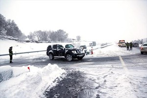 Agentes de la policía ayudan el domingo a los vehículos atrapados en la AP-6 por la tormenta de nieve.