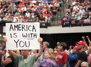 """Un seguidor de Trump muestra un cartel con la frase """"América te ama"""" en el mitin del presidente de Iowa."""