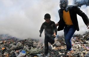 Un hombre saca a un niño de una humareda en la ciudad de Alepo.