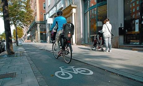 Un ciclista avanza por un carril bici bien delimitado en la acera, en el centro de Estocolmo.
