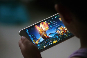 A child is pictured as he plays the game Honour of Kings by Tencent at home in Dezhou