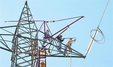 Un grupo de trabajadores preparan la sustitución del tendido de electricidad de una torre de alta tensión.