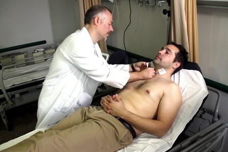 Un médico coloca sobre el paciente los sensores para hacer el análisis de sangre no invasivo.