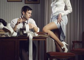 Una mujer muestra su pierna de hombre de negocios en el escritorio