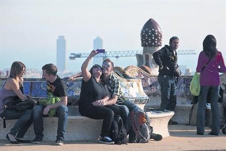 Una pareja de turistas se fotografía en uno de los bancos del parque Güell, ayer.
