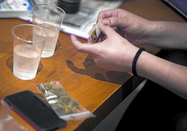 Un socio de un club prepara un porro de marihuana.