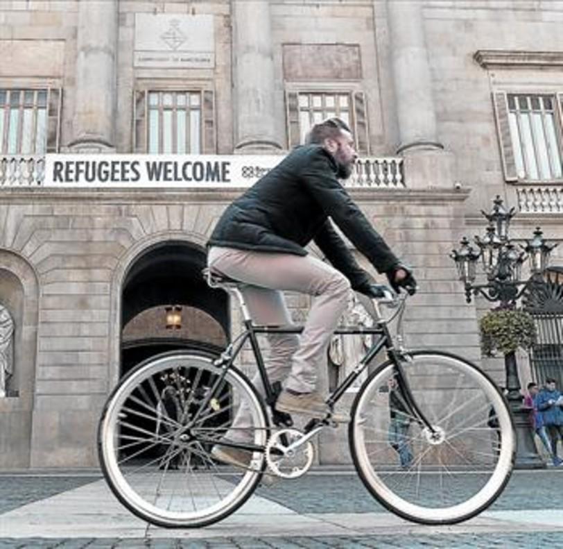 SOLIDARIDAD Un ciclista pasa por delante del Ayuntamiento <br/>de Barcelona, donde un cartel da la bienvenida a los refugiados.