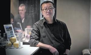El escritor de ciencia ficción Liu Cixin posa en un céntrico hotel de Barcelona, el lunes. A la derecha, portada de El problema de los tres cuerpos (Nova).