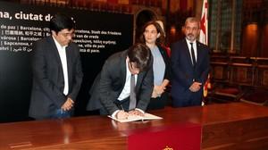 Puigdemont firma en el libro de condolencias del Ayuntamiento de Barcelona, acompañado por la alcaldesa, Ada Colau.