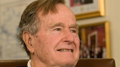 George H.W. Bush sonríe al escuchar al candidato presidencial republicano Mitt Romney, a quien apoyó en la elección del 2012, en un acto en Houston, el 29 de marzo del 2012.