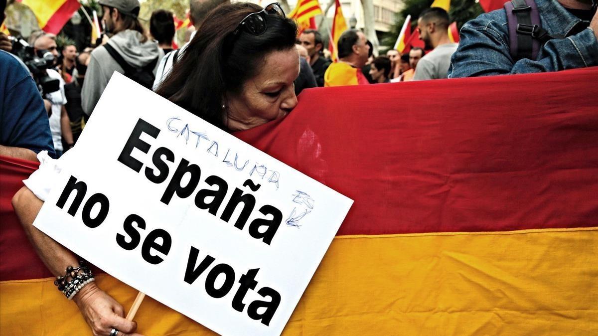 Una participante en la manifestación en contra del referéndum de la plaza Urquinaona besa una bandera de España.