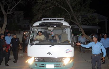 Agentes paquistanís escoltan el vehículo en el que viajan los familiares de Osama bin Laden, el jueves en Islamabad.