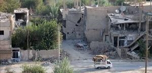 Una 'pick-up' circula junto a edificios destruidos en Deir Ezzor, en el este de Siria, este lunes.
