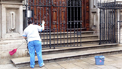Una mujer limpia la entrada de la catedral de Granada, este lunes.