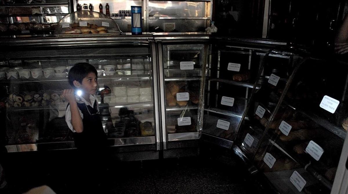 Un chico usa una linterna durante un corte de luz, en una panadería, en San Cristóbal, el 25 de abril.