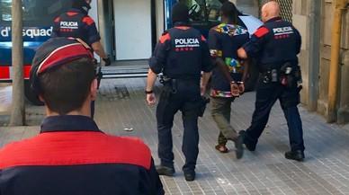Agentes de los Mossos se llevan a uno de los detenidos en la operaci�n contra el 'top manta' en Barcelona
