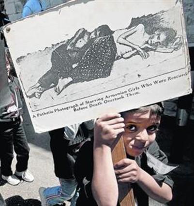 Un niño porta una pancarta con una imagen del genocidio armenio.