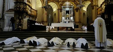El arzobispo Francisco Javier Mart�nez y otros curas, postrados en la catedral de Granada, el domingo.