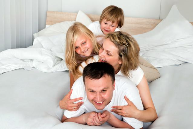 Un matrimonio con sus dos hijas en la cama