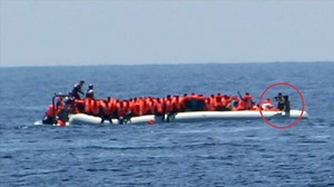 Imagen de la oenegé Jugen Rettet donde se ve a unos guardacostas libios apuntando a unos refugiados.