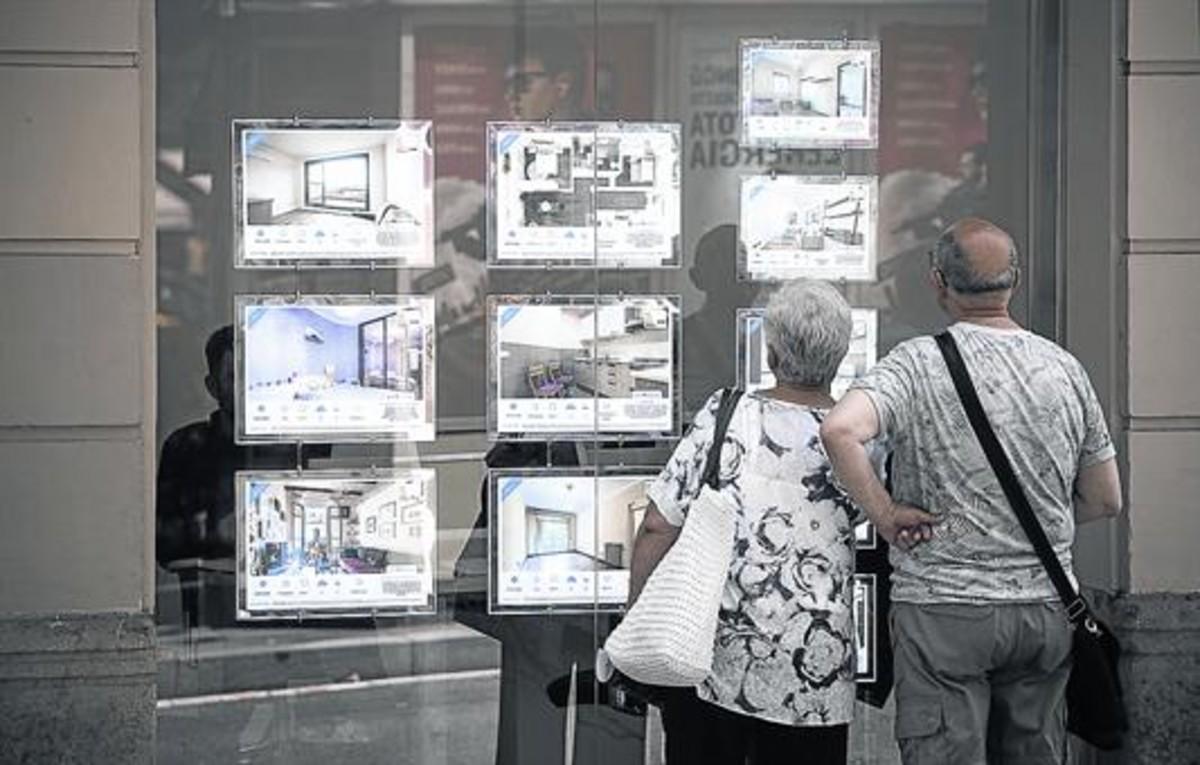 Una pareja observa ofertas de compraventa y alquiler de pisos en el escaparate de una agencia inmobiliaria de Barcelona.