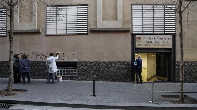"""Un trabajadorborra la aparición de la palabra """"culpables"""" sobre la fachada del colegio de Les Corts."""