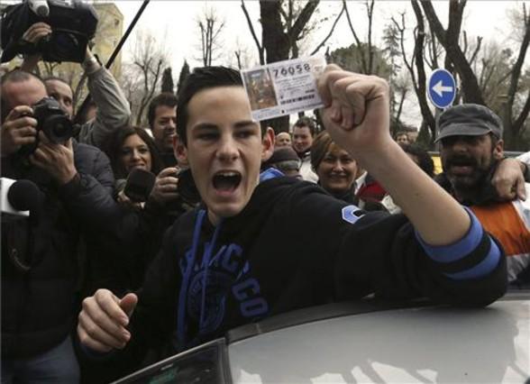 Un joven muestra un décimo del número 76.058 que ha sido agraciado con el primer premio de la Lotería de Navidad comprado en Alcalá.