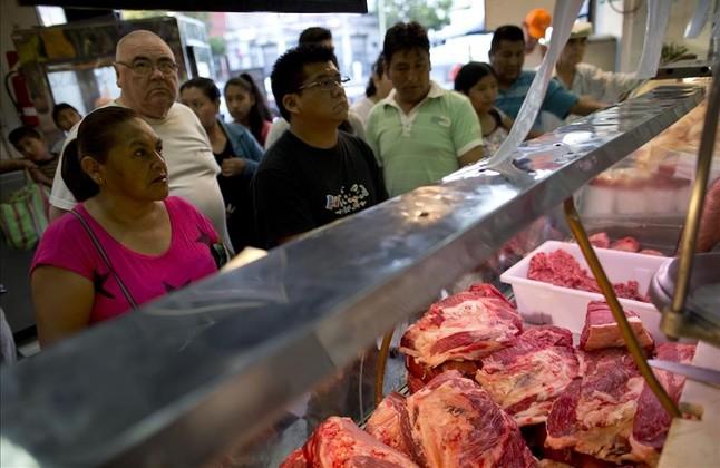 Unos clientes compran carne en un mercado de Buenos Aires.