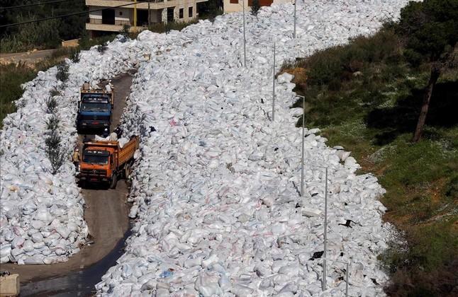 Camiones de basura pasan entre una montaña de desperdicios acumulados en una calle del suburbio de Jdeideh, en el norte de Beirut, este jueves.