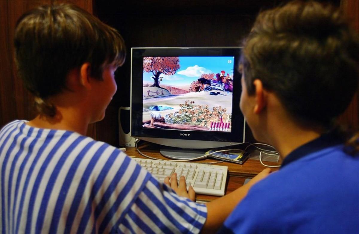 Dos niños, ante una pantalla de ordenador.
