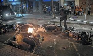 Un antidisturbios observa motos afectadas por los actos vandálicos durante las protestas en Gràcia contra el desalojo del banc expropiat.
