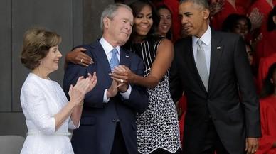 La primera dama, Michelle Obama, abraza al expresidente George Bush, en el momento de llegar con Obama a la inauguraci�n del museo de �frica inaugurado en Washington.