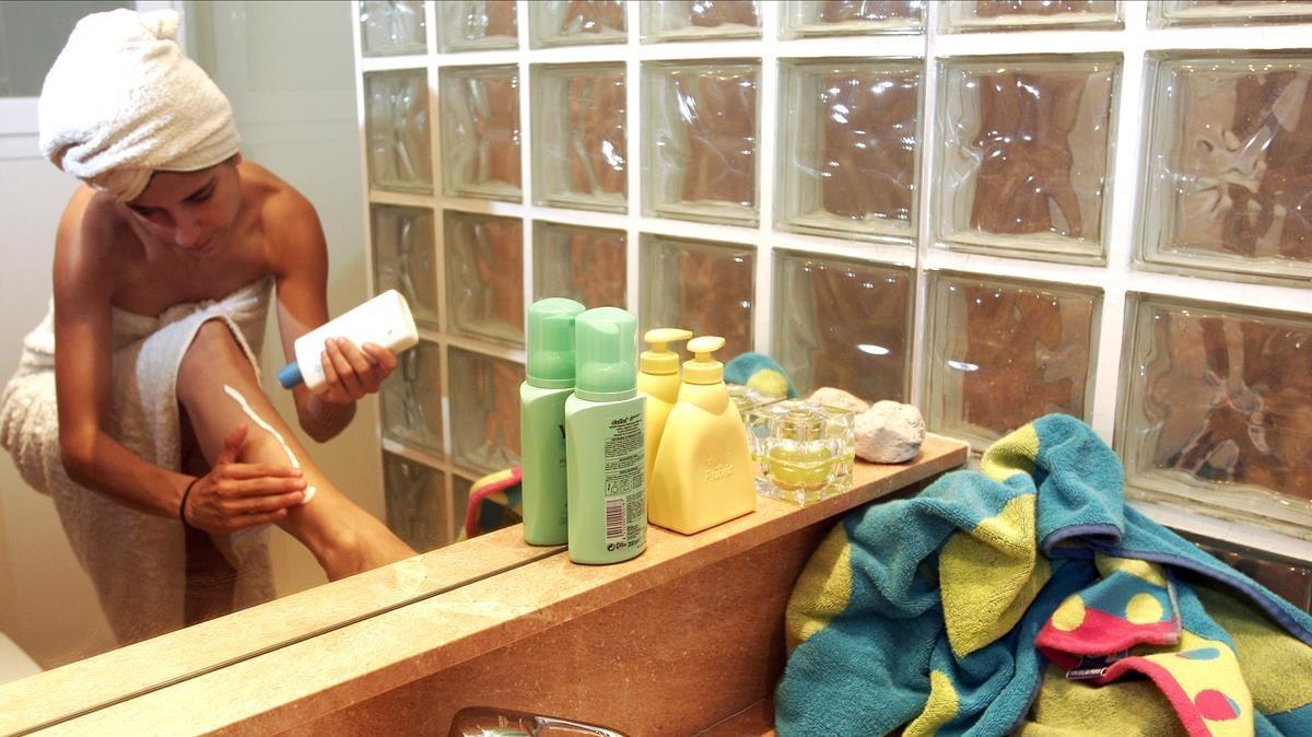Una mujer se aplica aftersun en el baño.