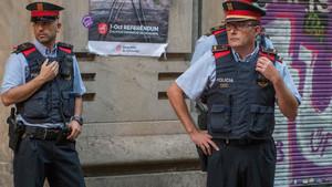 Agentes de los Mossos, ante un cartel del referéndum del 1 de octubre
