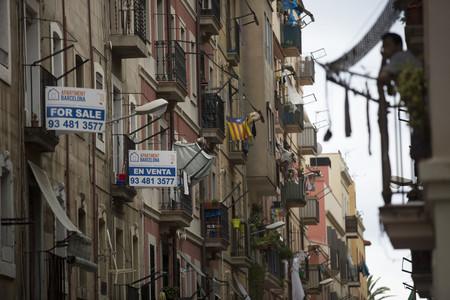 Anuncis de venda de pisos en castellà i anglès en un carrer de la Barceloneta.