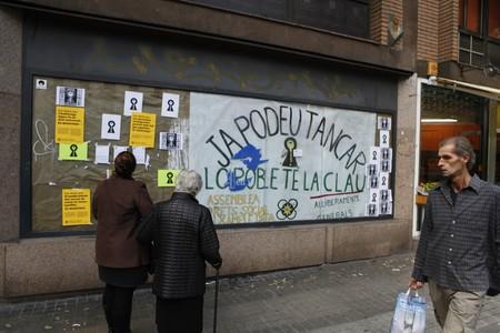 Carteles de la 'okupación' desde fuera de la oficina a la que han entrado los activistas.