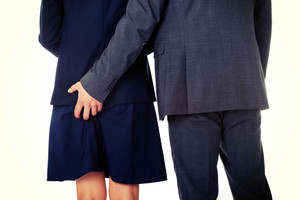 Joven empresario sosteniendo la mano en el culo de una mujer