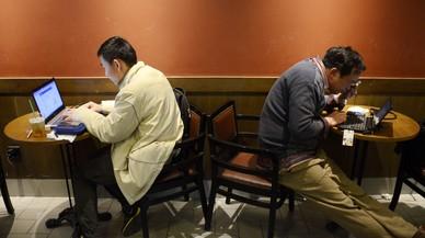 Dos hombres usan sus portátiles en un café de Shanghái.