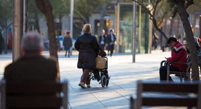Una mujer empuja la silla de ruedas de una persona dependiente en Barcelona.