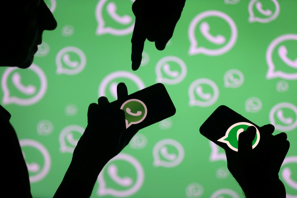 FILE PHOTO: Men pose with smartphones in front of displayed Whatsapp logo