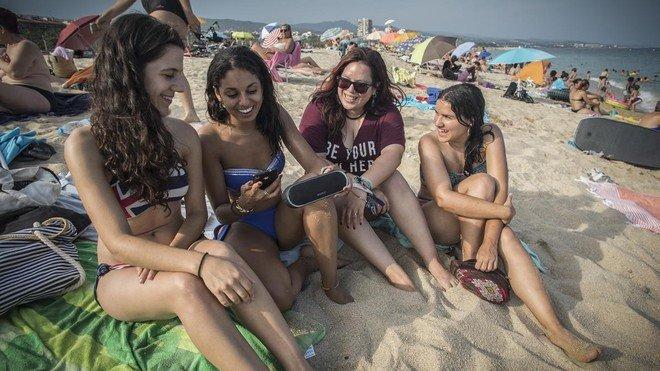 Un grupo de chicas escucha múscia en la playa con un altavoz bluetooth