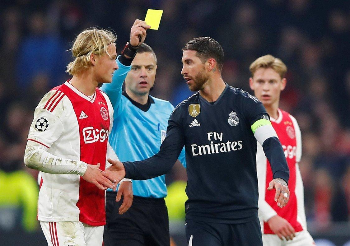 Sergio Ramos (d) recibe la amarilla durante el partido contra el Ajax.