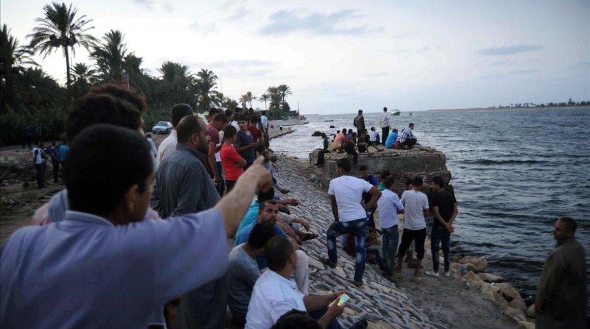 Allegados de las víctimas observan las tareas de rescate del naufragio en Egipto.