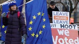 Una activista anti-brexit exhibe una bandera europeajunto a un partidario de abandonar la UE en Londres.