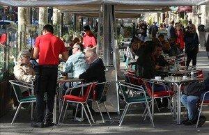 Un camarero atiende a clientes en una terraza. Es el colectivo con más contratos temporales.