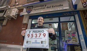 José María Imbernon, gerente de la administración La Bruja Rockera, en Murcia, muestra el cartel del segundo premio del Niño.