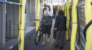 Un ciclista y una transeúnte comparten acera bajo un andamio en Urgell con Provença.