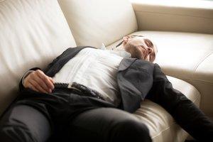 FOTO BAJADA DE 123RF EL 3 DE MAYO DEL 2019 PARA ILUSTRAR UN ARTICULO SOBRE CATAPLEXIA / NARCOLEPSIA. HOMBRE DORMIDO EN UN SOFA. DORMIR. DESCANSAR. DESMAYO. DESMAYADO. SIESTA. Close up of exhausted businessman laying on the couch. Young hard working entrepreneur fell asleep on sofa at workplace. Staying at work overtime, overworked, too much workload, lack of sleep concept. FOTO DE Aleksandr Davydov / 123 RF