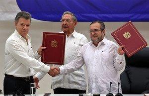 El delegado de las FARC en Cuba, Rodrigo Londoño Echeverri, alias Timochenkoy el presidente de Colombia, Juan Manuel Santos, junto a el presidente de Cuba, Raúl Castro sostienen en sus manos el acuerdo de paz entre el Gobierno colombiano y las FARC.