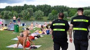 Dos agentes de seguridad vigilan que los bañistas cumplan la distancia de seguridad en Neckartailfingen, en el sur de Alemania.
